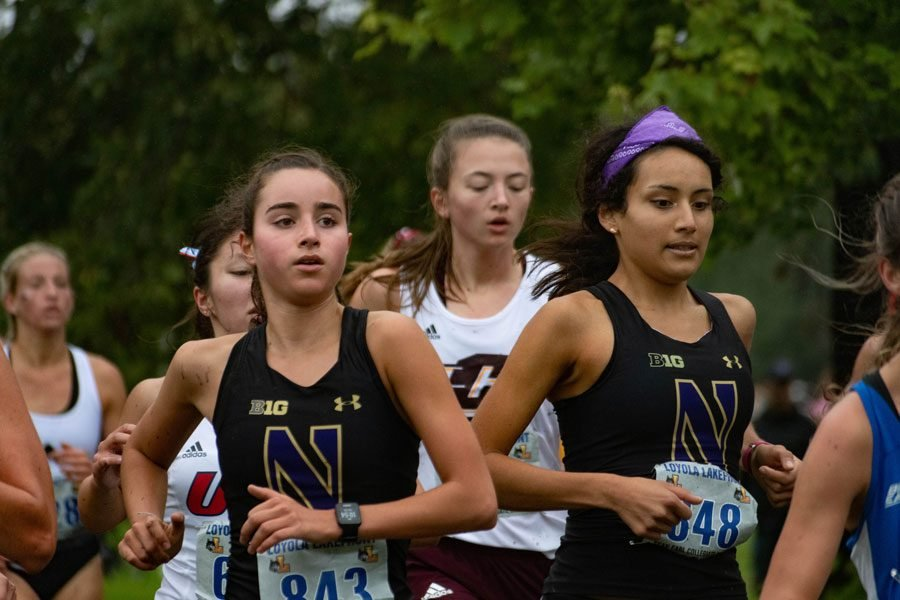Two female runners race side by side wearing black and purple jerseys.