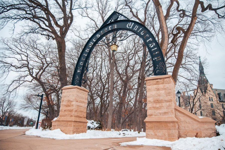 A photo of the Arch in winter. There is snow on the ground and multiple trees in the background set against a gray sky.