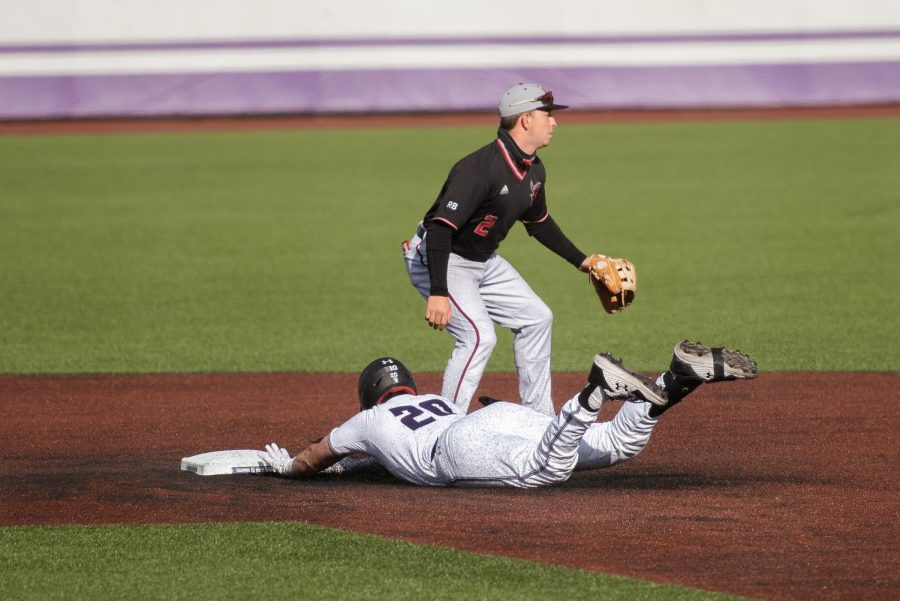 Player in white jersey dives across brown dirt to white base stood over by player in black jersey