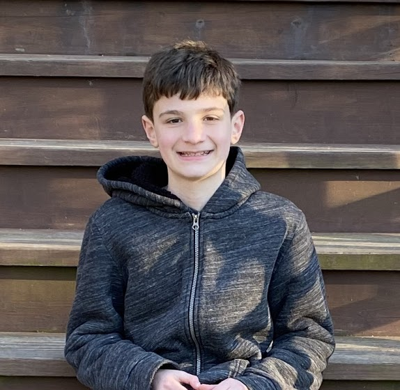 Photo of 13-year-old boy wearing a black sweatshirt and sitting on stairs.