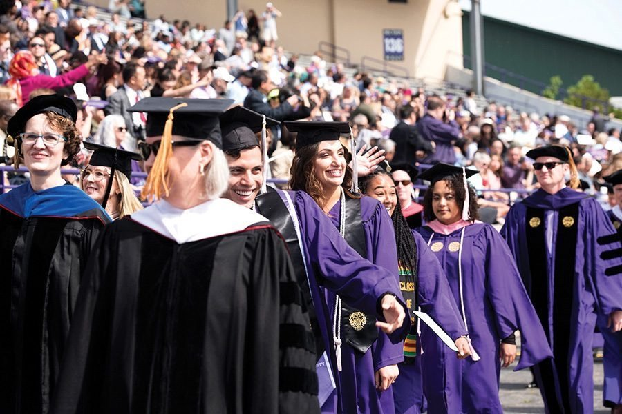 Smiling+people+in+purple+and+black+garb+and+graduation+caps+walk%2C+with+two+people+in+black+commencement+uniform+in+the+front.+In+the+background+are+a+blurred+crowd+of+people+in+waving+motion.