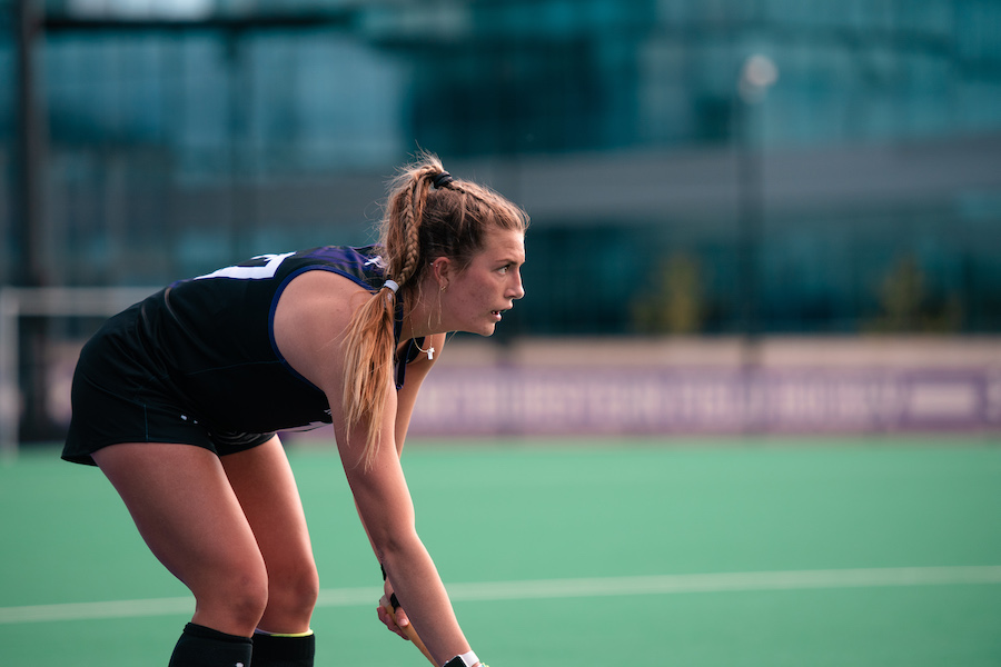 Girl with long blonde hair in ponytail in black bends down with field hockey stick in hand