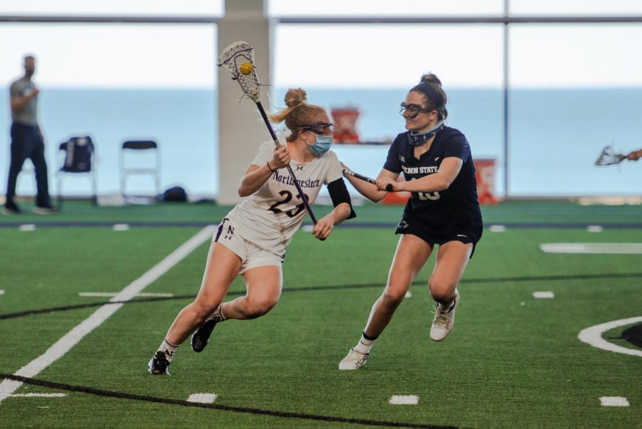 Lacrosse player Lindsey McKone runs down the field with her lacrosse stick.