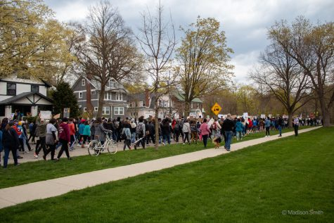 Residents and students march in a dense crowd along the street between a row of houses and a lawn of grass.