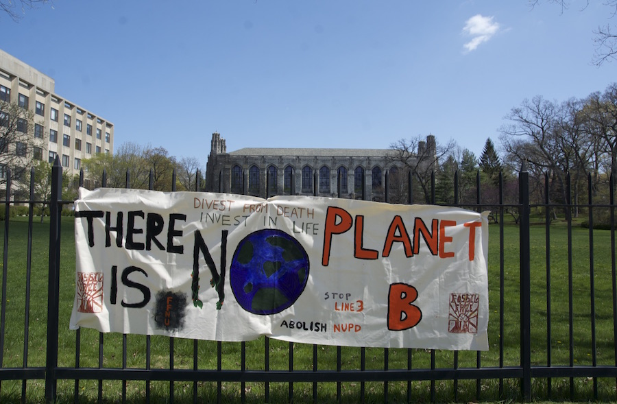 """Banner reading """"There is no planet B,"""" with a drawing of the earth in the center. Banner also reads """"Divest from death, invest in life,"""" """"Stop Line 3"""" and """"Abolish NUPD."""" It is hanging on a black fence in front of the Deering Library."""