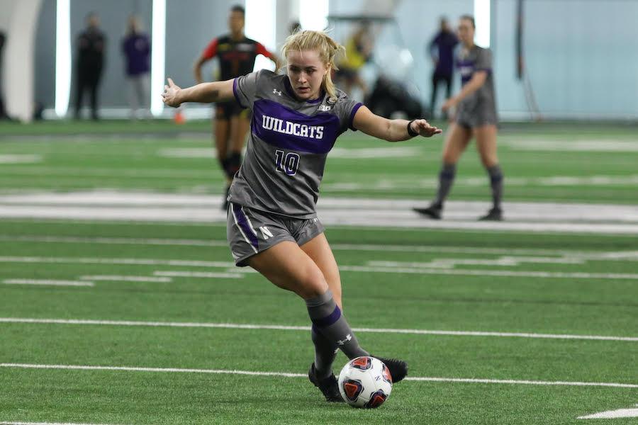 Women's soccer player dribbles soccer ball.