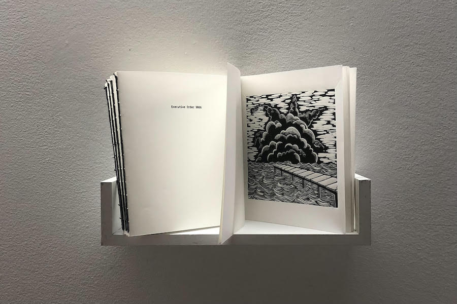 """A booklet stands open on a shelf. On one page, the text """"Executive Order 9066"""" is printed. On another, a black and white ink print of an explosion on a body of water, meant to represent the bombing of Pearl Harbor."""
