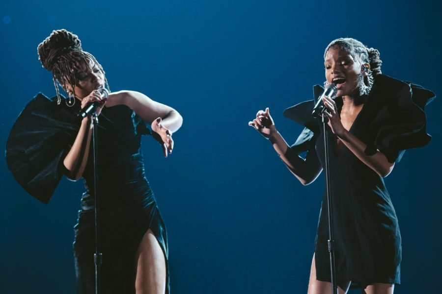 Chloe x Halle perform in black dresses facing toward each other. The background is dark blue.