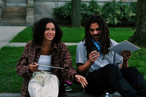 Sitting on the curb, with green grass behind them, a couple are captured smiling together, holding art canvases.