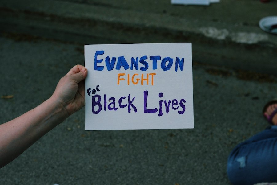 """In blue, orange, and purple paint a sign reads """"Evanston Fight for Black Lives."""" It is held up by a left hand and other people can be seen in the background, sitting down."""