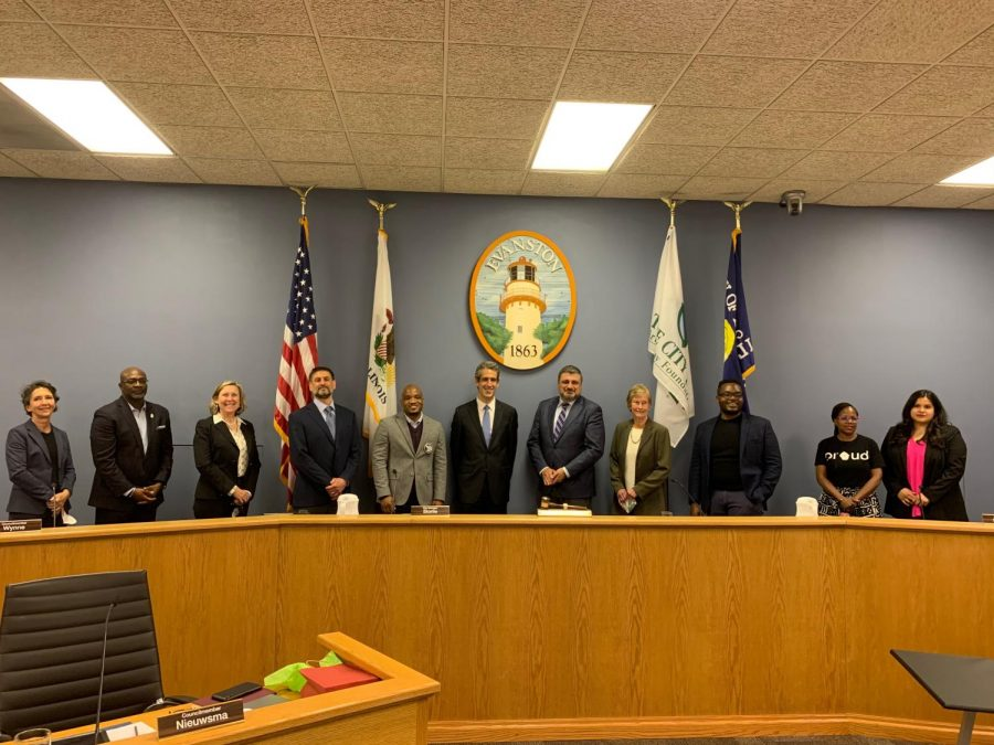 The new City Council stands behind the lectern on the dais shoulder to shoulder.