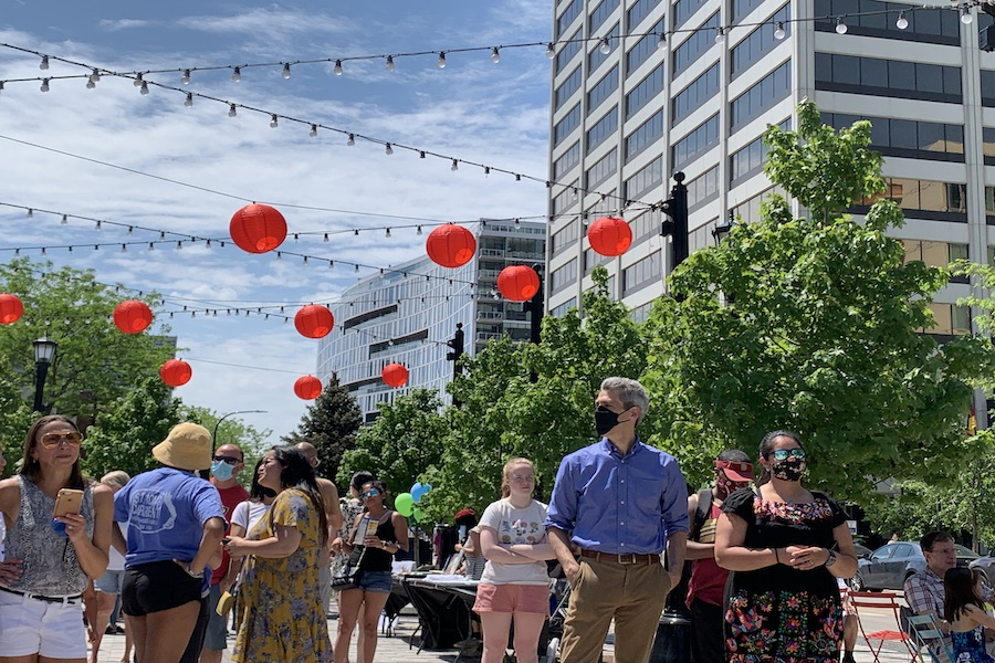 Groups of people talk with each other in a city square lined by green trees. Red lanterns on white strings criss-cross the blue sky.