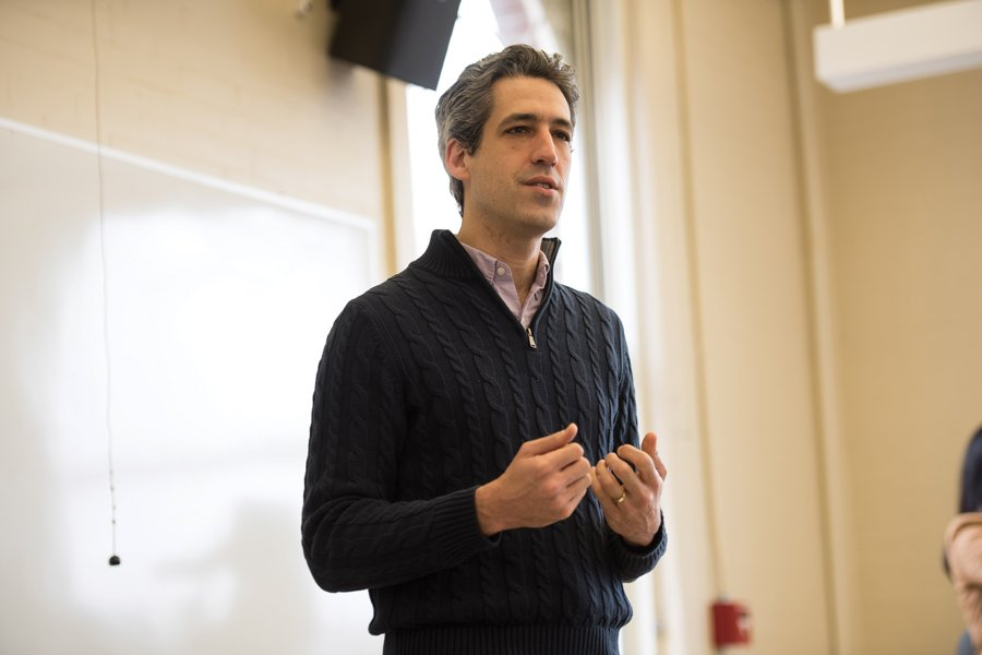 Daniel Biss speaks in Fisk Hall. He is wearing a black sweater.