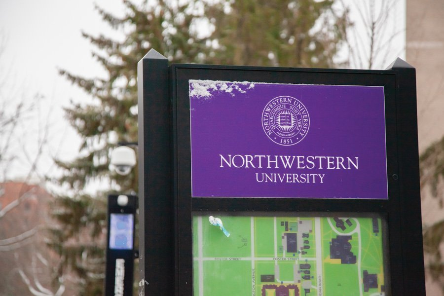 """A photo of a rectangular sign that says """"Northwestern University"""" behind a purple background in white font. There is a bit of snow on the sign. Below the sign is a portion of a map of the University that's mostly green with paths to show roads and sidewalks. Behind the sign are a few trees scattered in the background."""