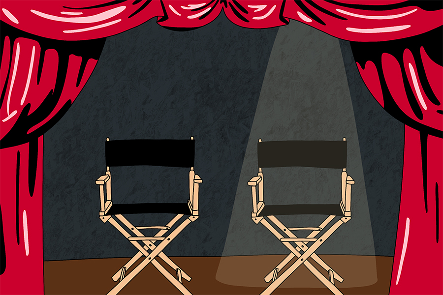 Two directors chairs sit on a stage surrounded by red curtains. The chair on the right has a spotlight.