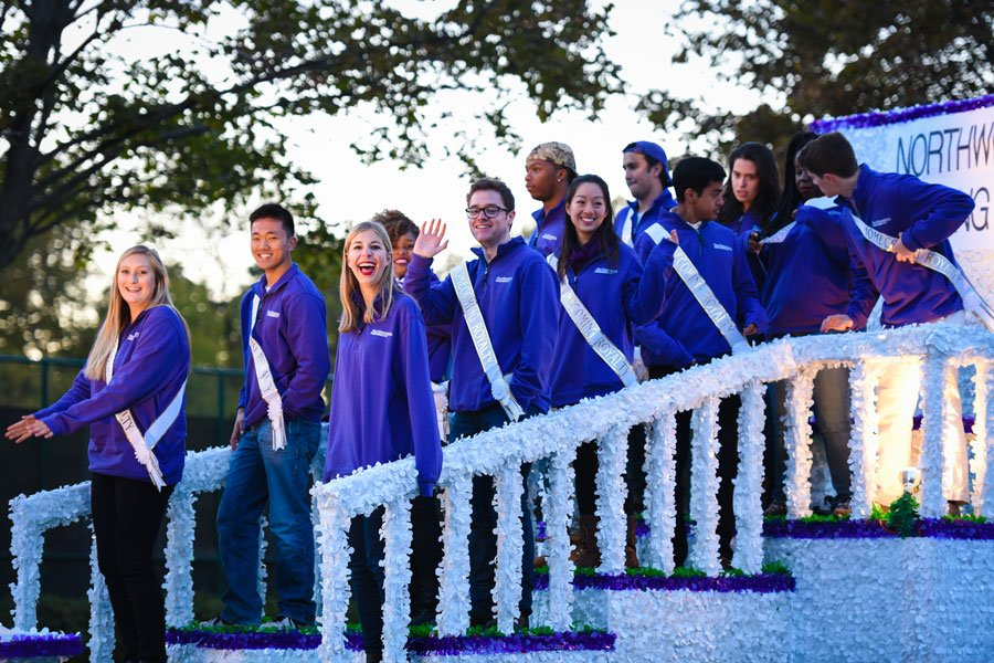 About 12 Northwestern students wearing purple jackets and white sashes stand on a white and purple parade float and smile at the camera waving.