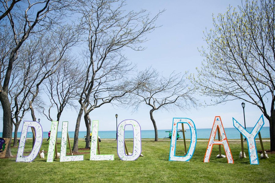 """Cardboard letters outlined in neon colors and splattered with paint. The letters spell out """"Dillo Day."""""""