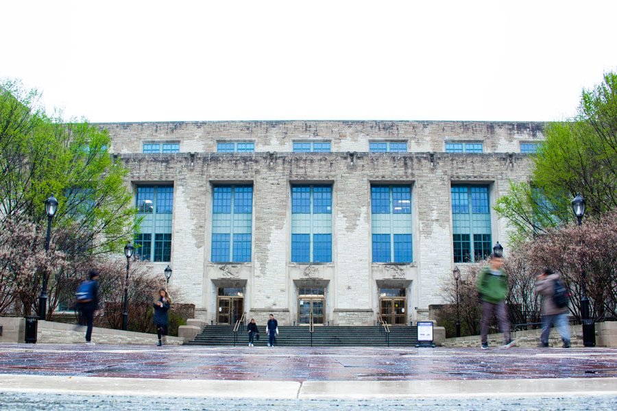 A photo of NU's Technological Institute. The concrete building has multiple stairs leading up to the entrance. There are seven large visible windows in the image of the building and some give off a blue hue because of the lighting. There are some trees with green leaves and other trees with pink leaves present along the sides of the building. Multiple students walk to and from the building and are slightly blurry.