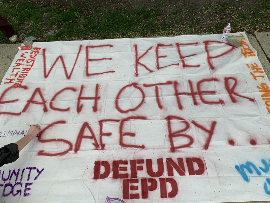 "A white banner with ""We Keep Each Other Safe By..."" written in red capital letters."