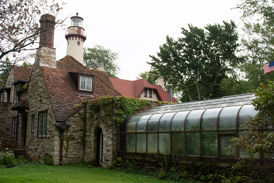 brick building with vines, trees, and lighthouse