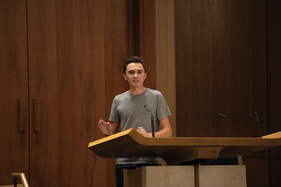 A photo of David Hogg speaking in front of a wooden podium behind with two small black microphones. He wears a gray shirt and dark blue jeans. The background is a wooden wall.