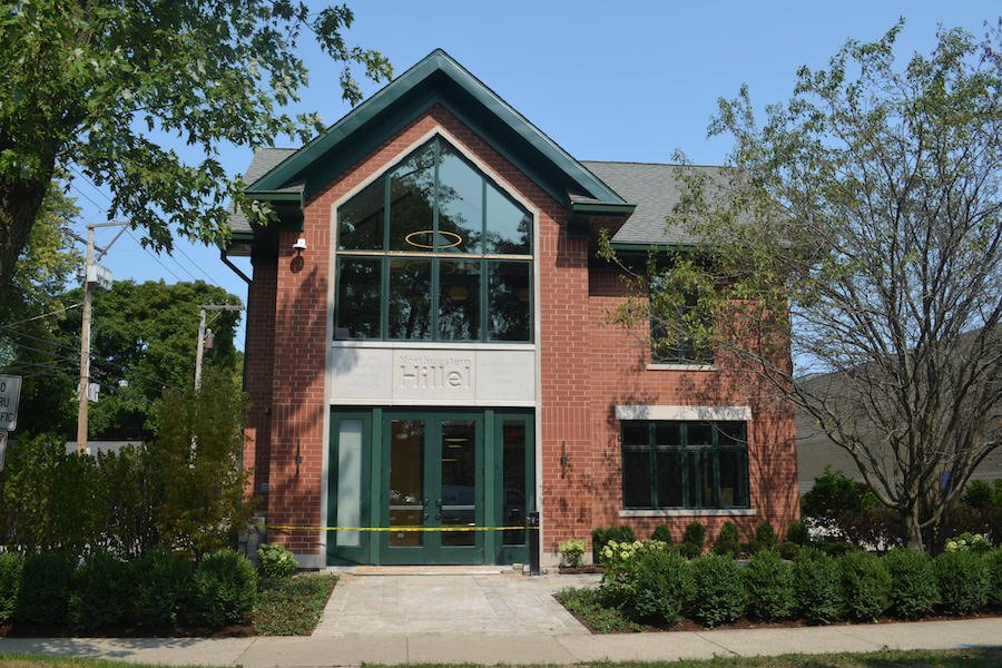 """Image of brick house with green window panes and green double doors. There are trees and shrubbery on the front lawn. Sign above the door reads """"Northwestern Hillel."""""""