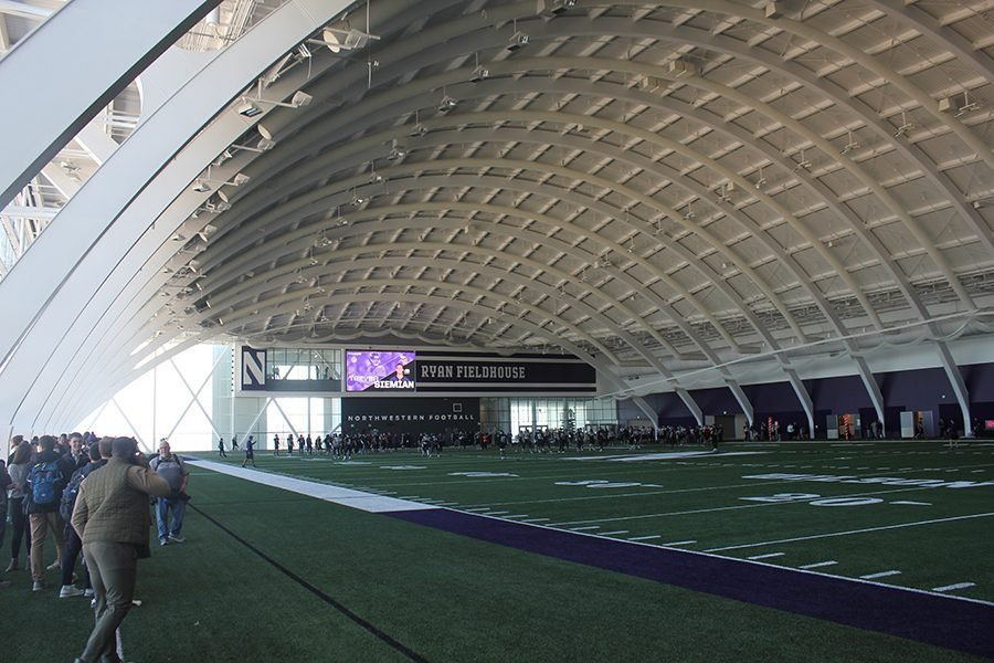 Green+field+with+purple+and+white+turf+with+white+curving+roof+on+top+of+building.