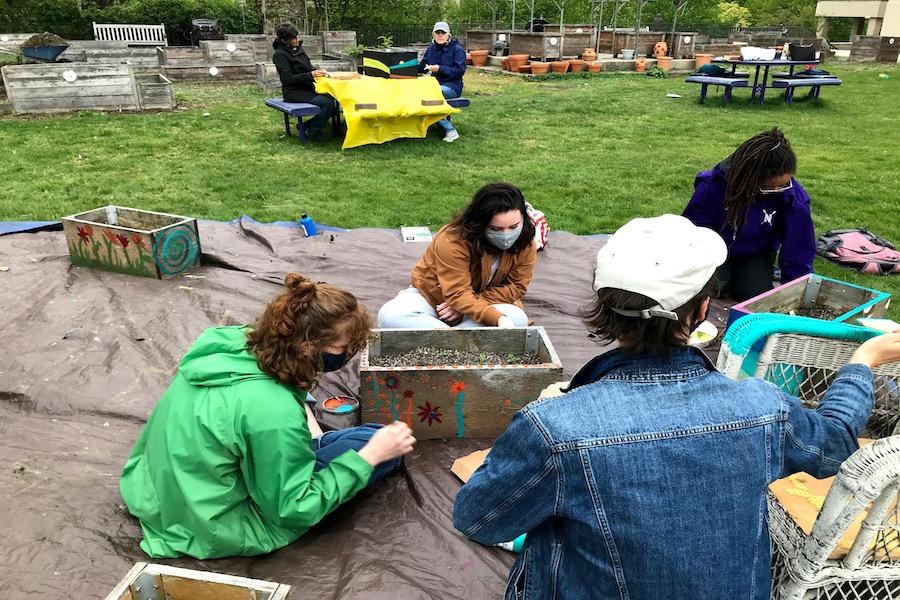 Four people sit on a blanket around wooden garden boxes. They are in the middle of a grass field and painting the boxes with flowers.