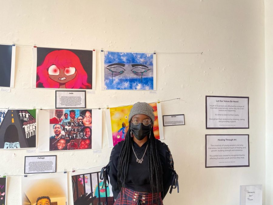 Artist Jayda Cochrane stands in front of her piece, a pair of crying eyes on a blue and gray background.