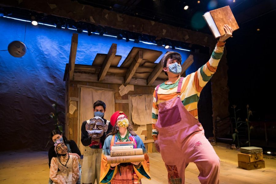 """Daniel Calderon (Communication '24) is dressed in costume and holds a book in hand in this photo of the Wirtz Center's production of """"Tomás and the Library Lady."""" Calderon's castmates appear in the background, all standing behind him. They are holding an assortment of books and puppets."""