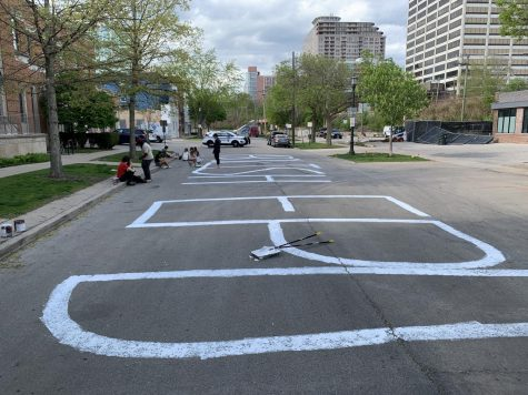"""A wide street with """"Abolish EPD"""" painted on it in white letters."""