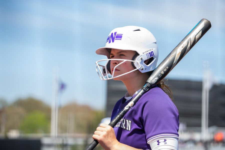 Girl with short brown hair in purple jersey looks to sky with bat in hand