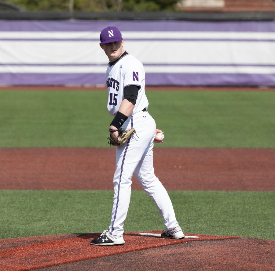 Northwestern player looks to first base between pitches.