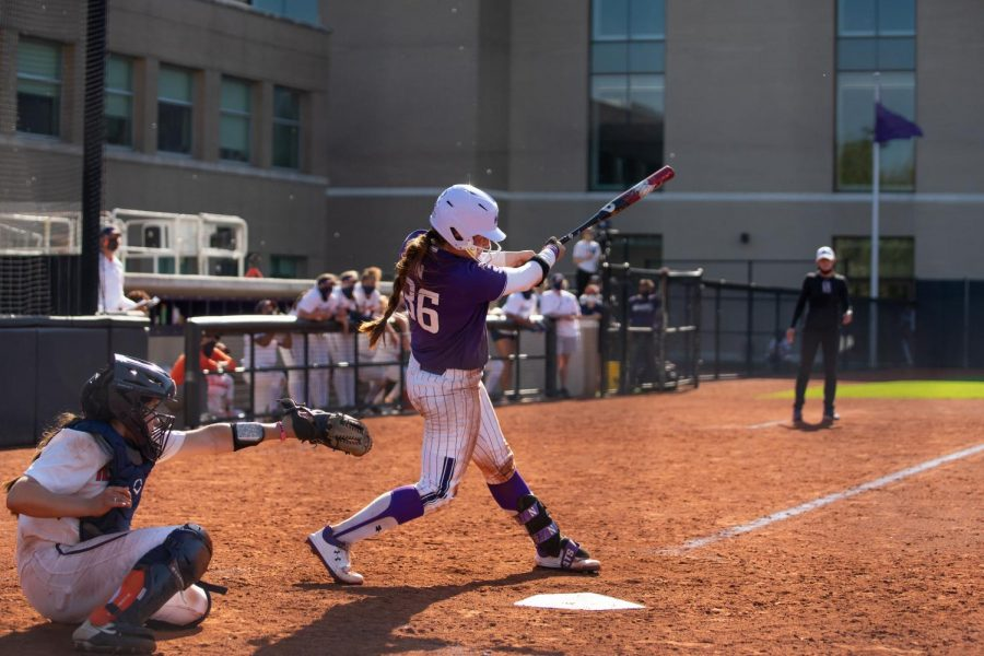 Northwestern softball player in white uniform swings at a pitch.