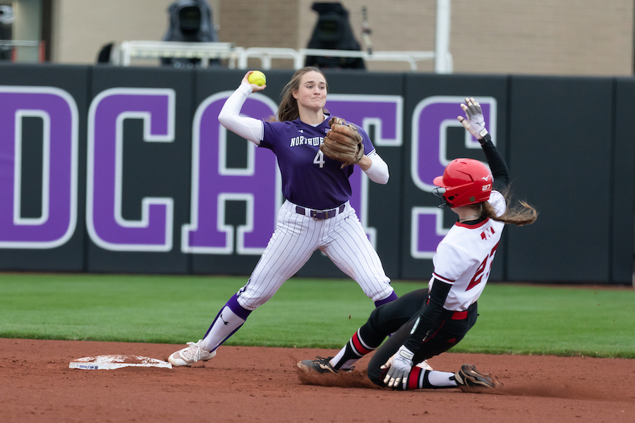 Northwestern softball player in purple uniform swings at an incoming pitch.