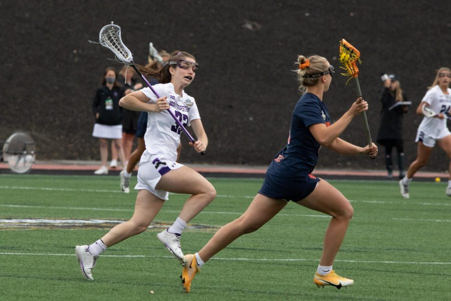 A lacrosse player wearing white holds her stick and runs down field to guard a player dressed in blue with an orange lacrosse stick.