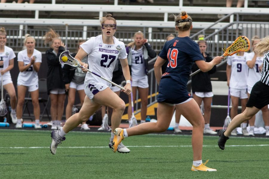 A lacrosse player wearing white with hair in ponytail runs down the field.