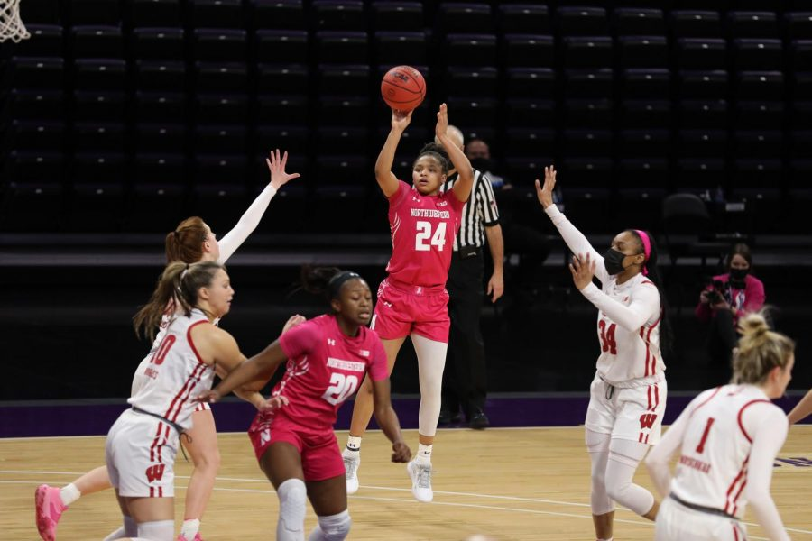 Girl in pink uniform with hair in short ponytail shoots the ball over other girls' hands.