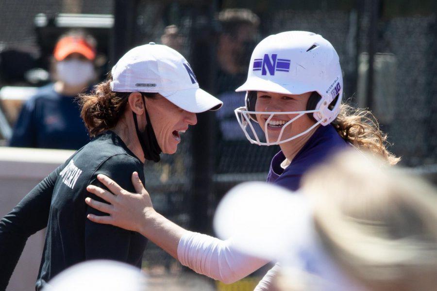 Softball player and coach celebrating.