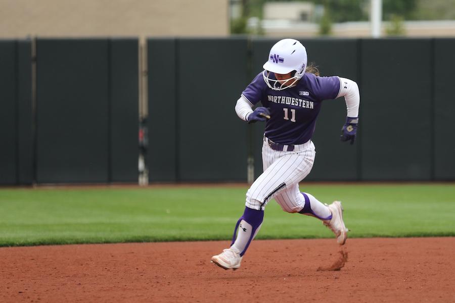 Northwestern softball player in purple uniform runs on the basepath.