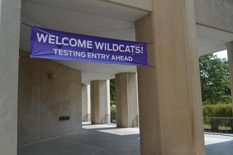 """The Donald P. Jacobs Center with tan pillars, with green shrubs in the background. The purple sign above states """"Welcome Wildcats! Testing Entry Ahead."""""""