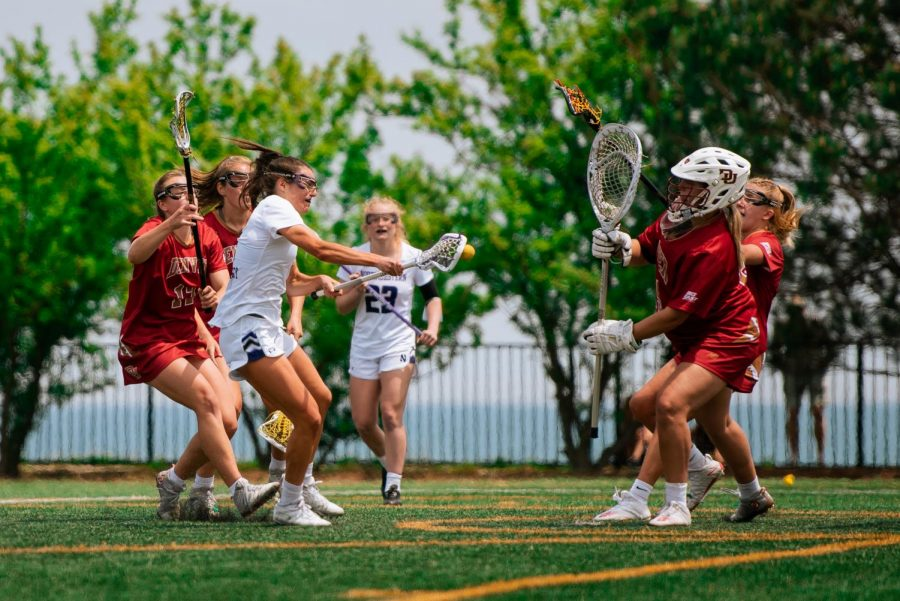 A lacrosse player wearing white with hair in ponytail shoots ball.