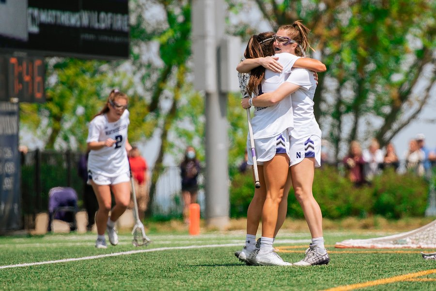 Two lacrosse players wearing white with hair in ponytails hug each other.