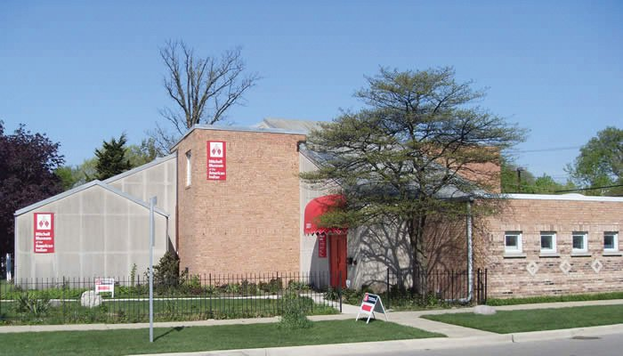 A side view of the Mitchell Museum, which is made of light brown bricks and has red rectangular signs with the Mitchell Museum logo.
