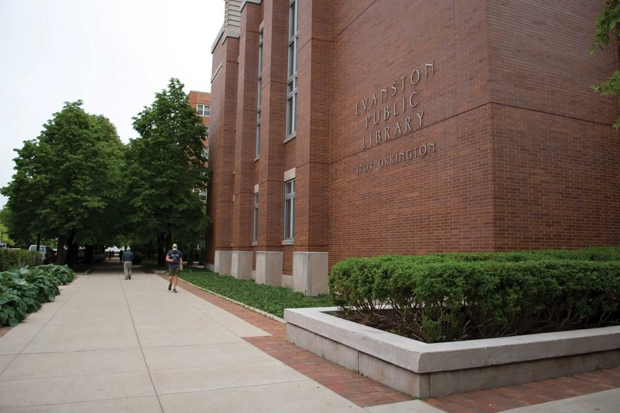 The exterior of Evanston Public Library. Two pedestrians walk on the sidewalk.