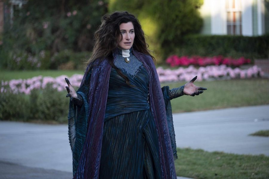 """Kathryn Hahn (Communication '95) in a scene from Marvel Studios' """"WandaVision."""" She stands in the center of the frame, and she wears a black witch's dress with a purple cape."""