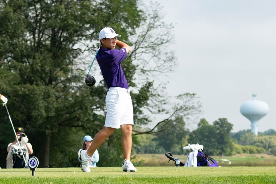 Golfer James Imai, wearing a purple shirt and white shorts, watches his shot while swinging through in front of a forest landscape and a distant water tower.
