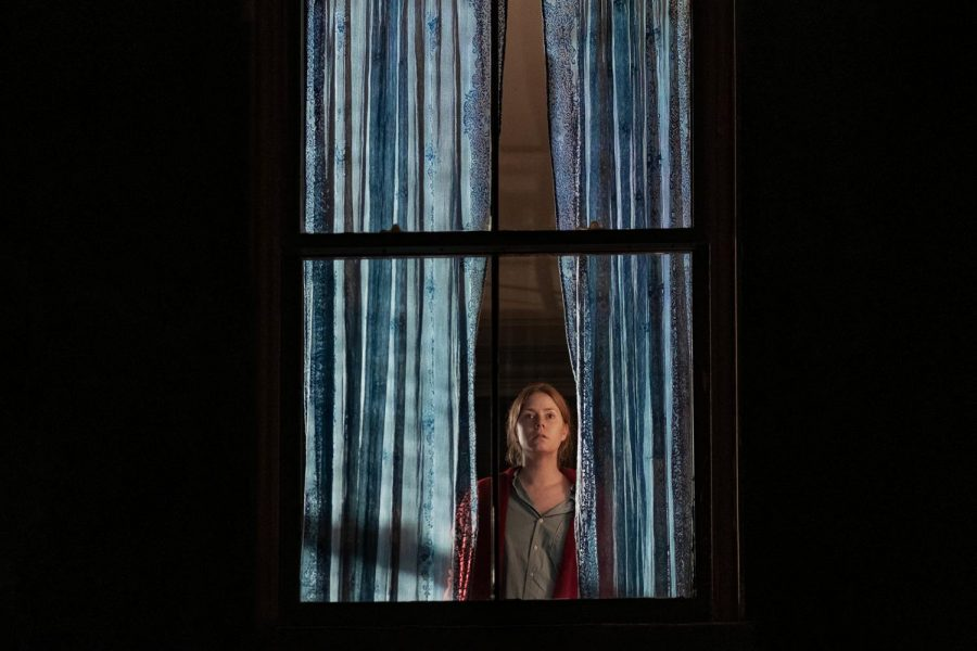 A woman stands in front of a window that has long curtains.