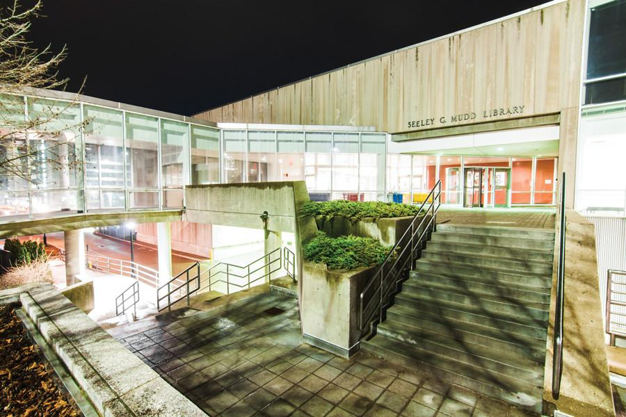 Photo of the Mudd Science and Technology Library at night. Building is lit and there is a staircase in the foreground.