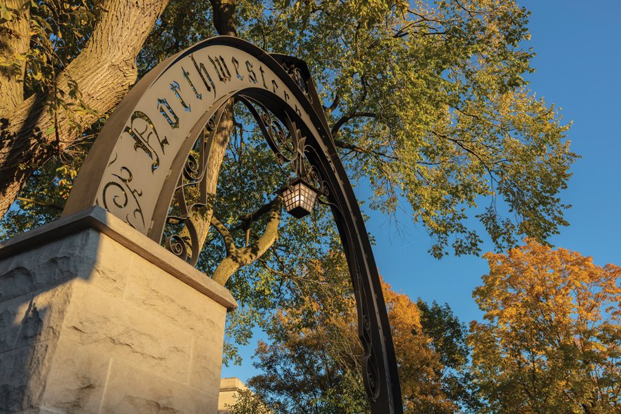 Northwestern's Weber Arch stands with a blue sky in the background. Tall trees and branches frame the Arch.